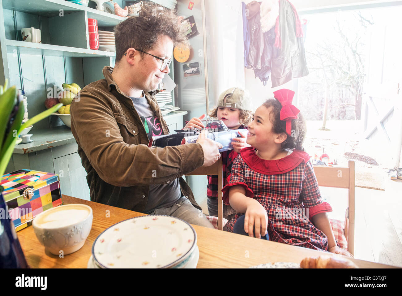 A father sits in his kitchen chatting to his young son and daughter. - Stock Image