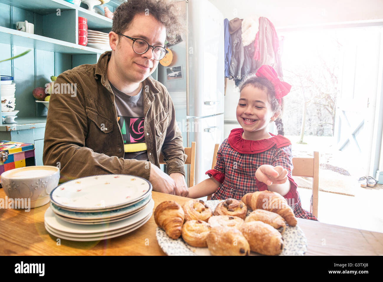 A father sits in his kitchen chatting to his 6year old daughter. - Stock Image