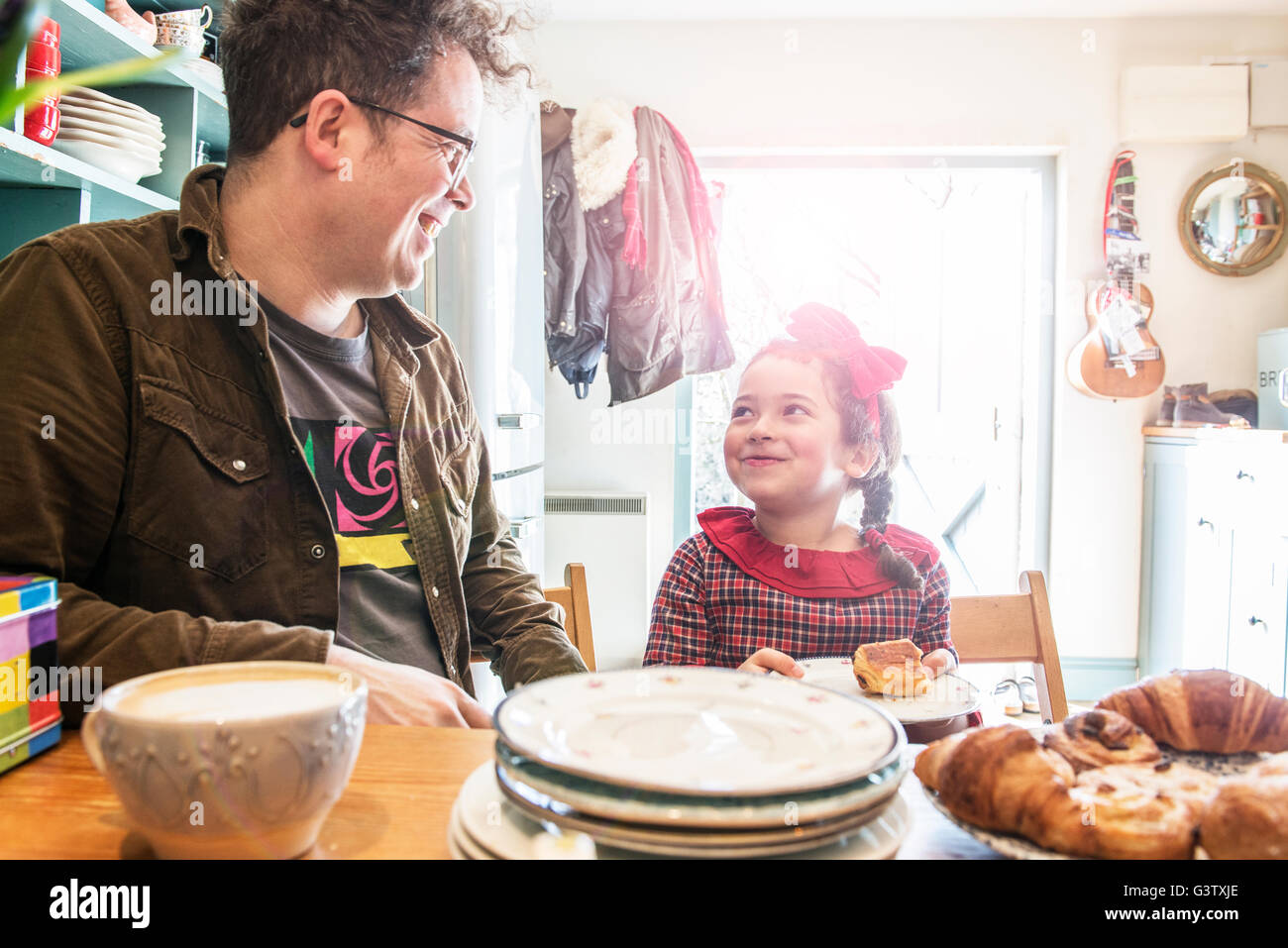 A father sits in his kitchen chatting to his 6 year old daughter. - Stock Image
