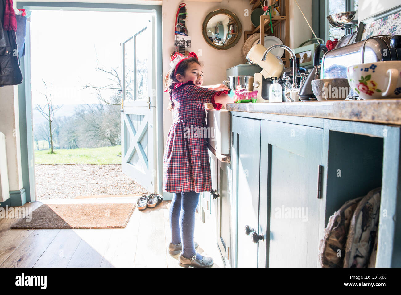 A six year old girl standing washing dishes in a kitchen sink. - Stock Image