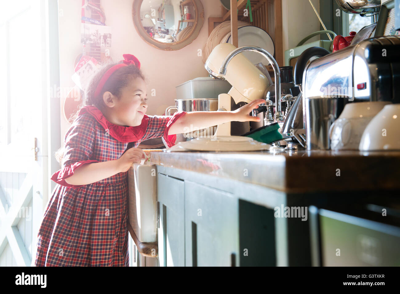 A six year old girl washing dishes at a kitchen sink. - Stock Image