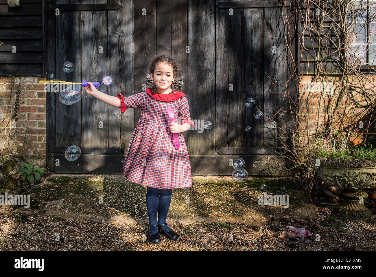 A six year old girl blowing bubbles by a garage door. - Stock Image