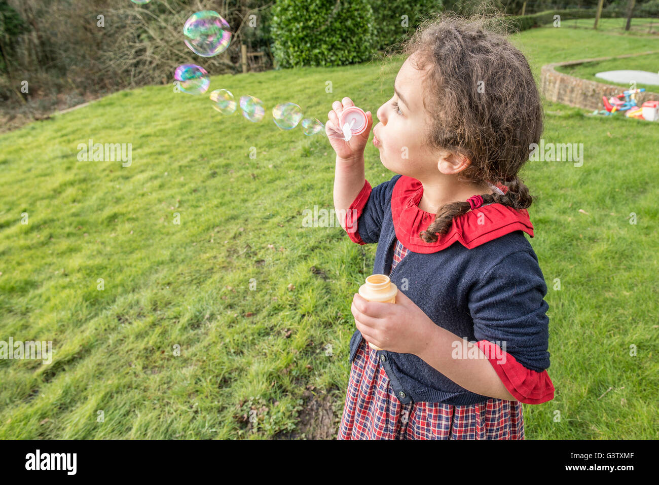 A six year old girl blowing bubbles in a garden. - Stock Image