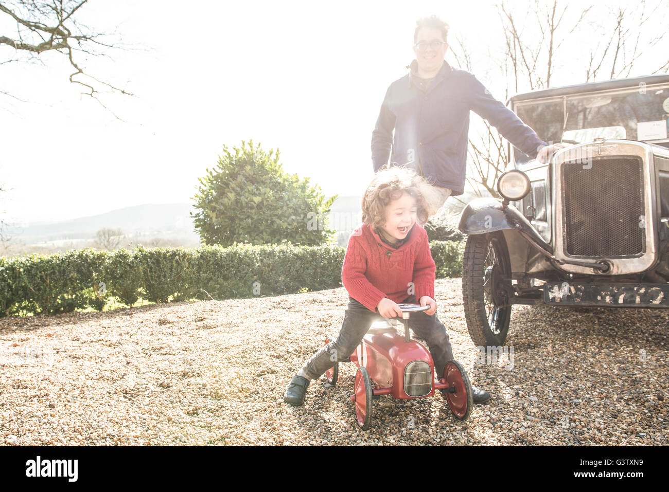 A four year old boy sitting sitting on a toy tractor watched by his father. - Stock Image