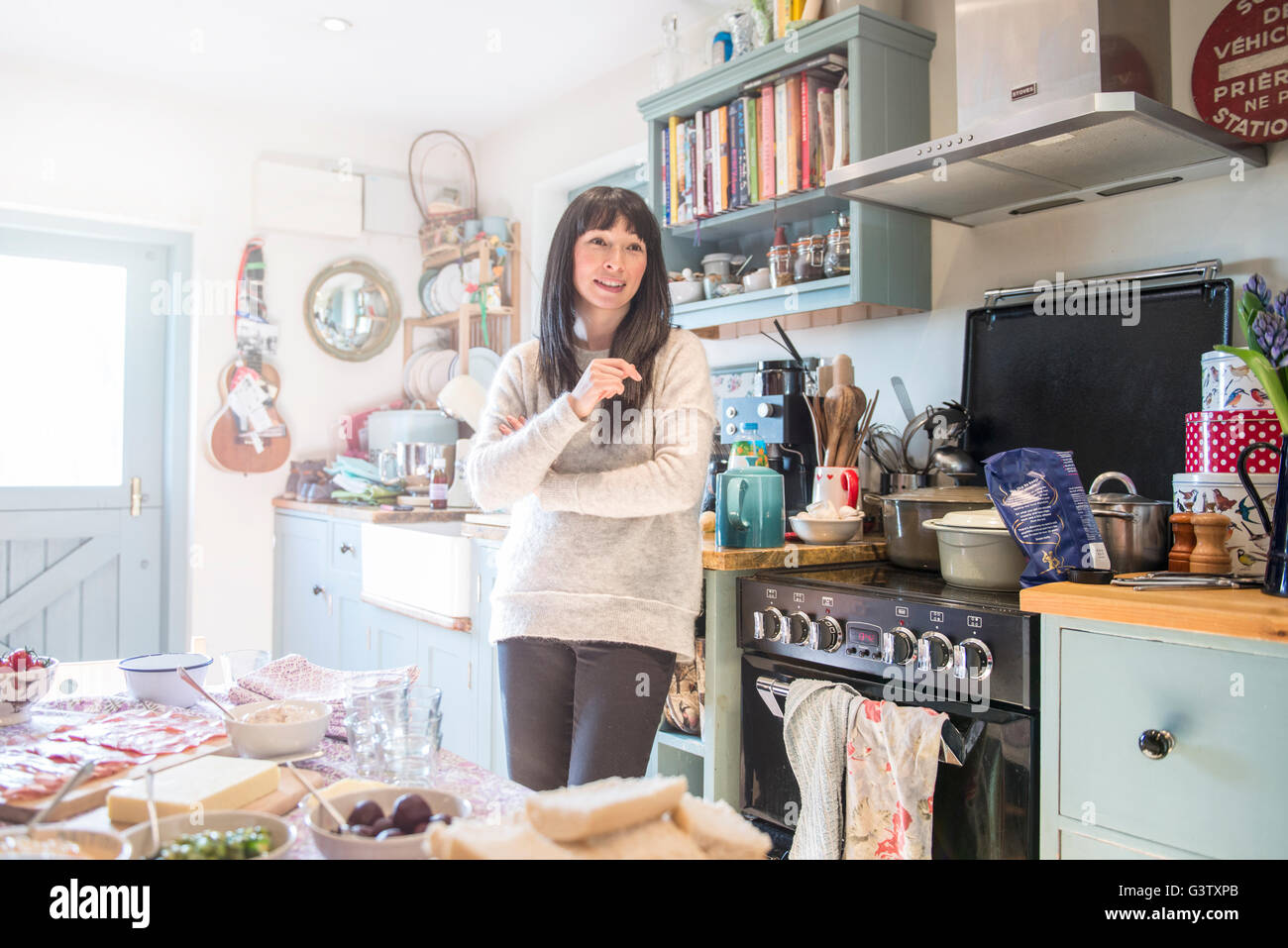 A dark haired woman standing chatting in a kitchen. - Stock Image
