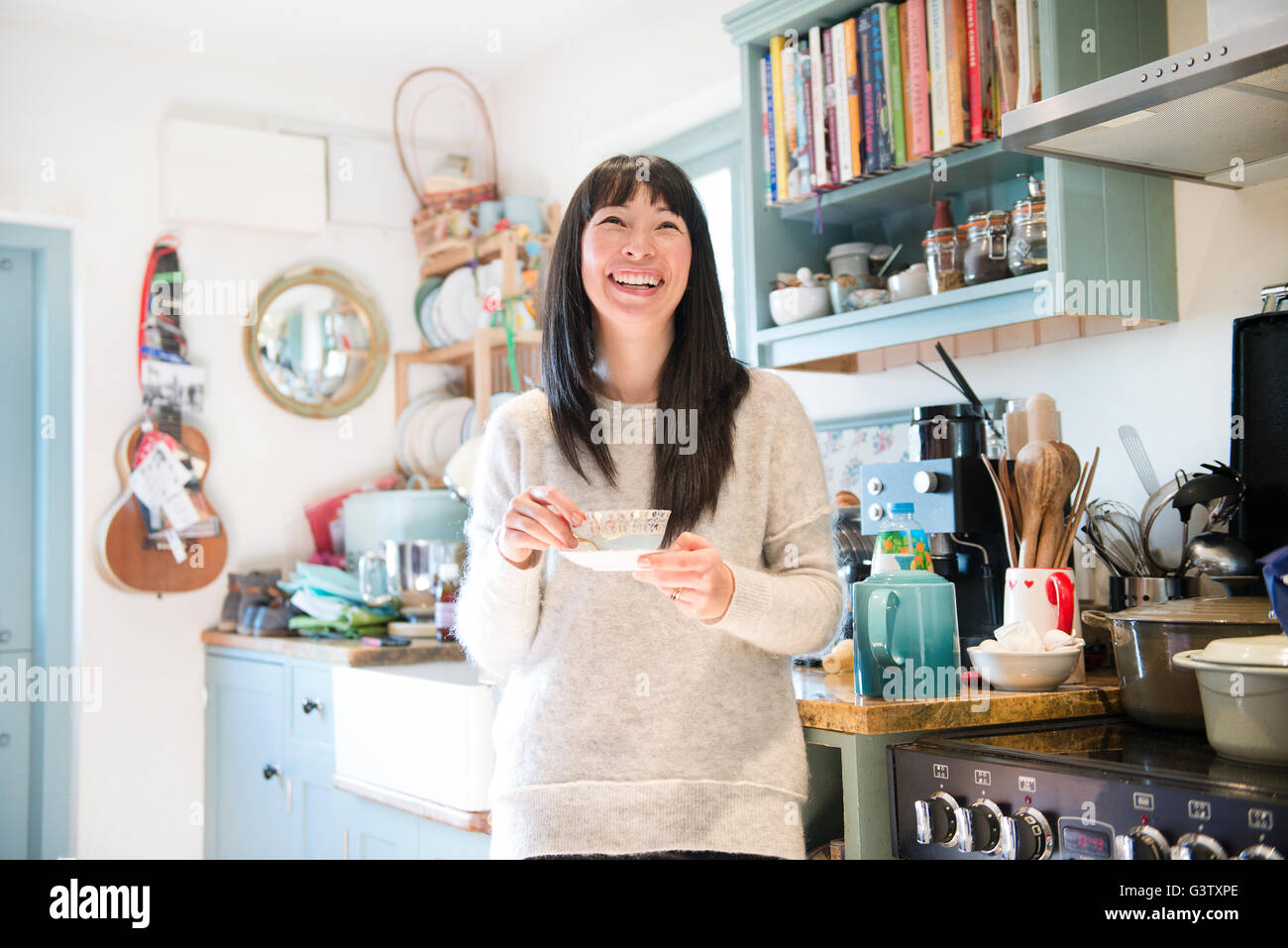 A dark haired woman standing in a kitchen chatting holding a tea cup. - Stock Image
