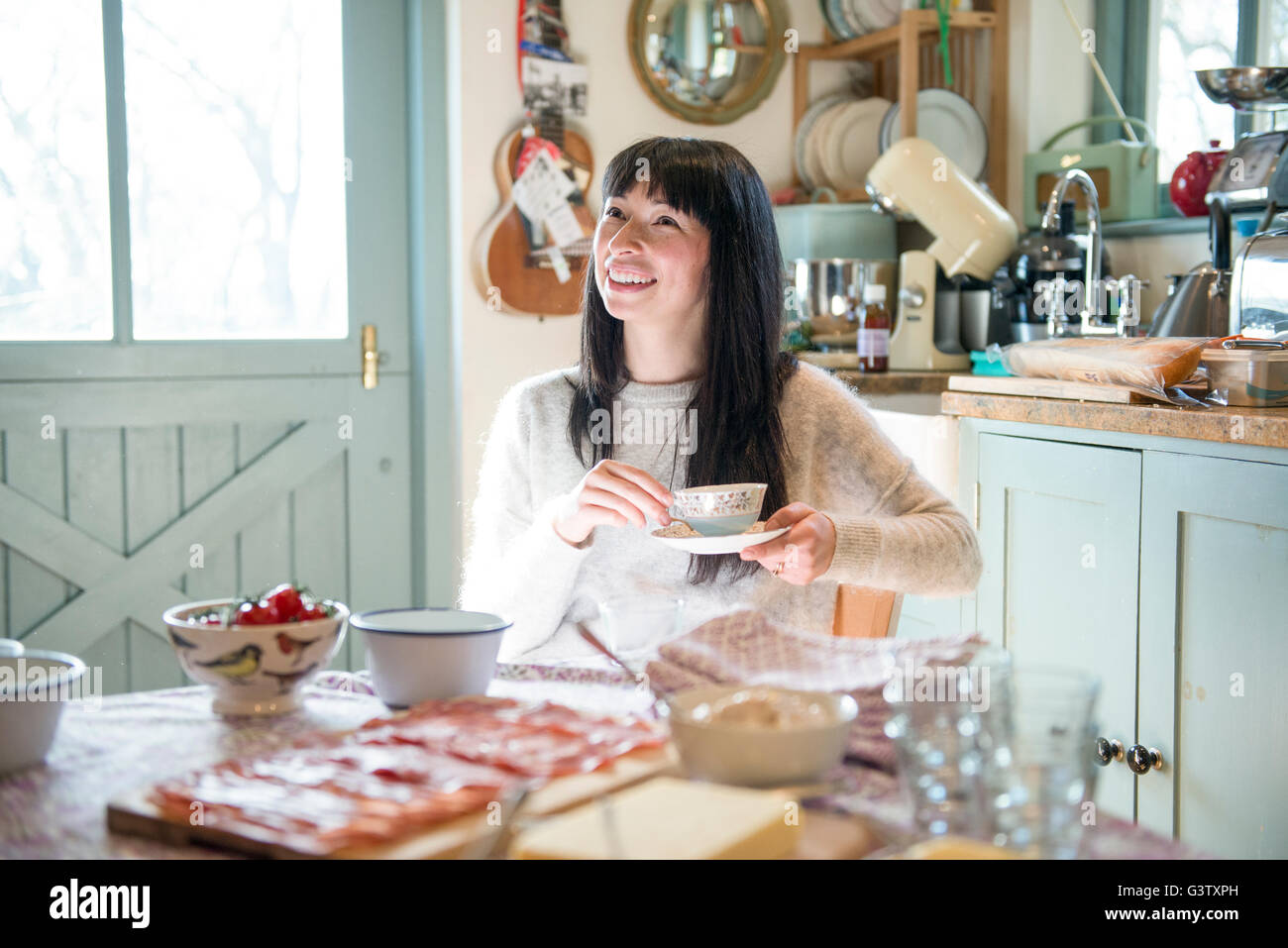 A dark haired woman sitting in a kitchen chatting holding a tea cup. - Stock Image