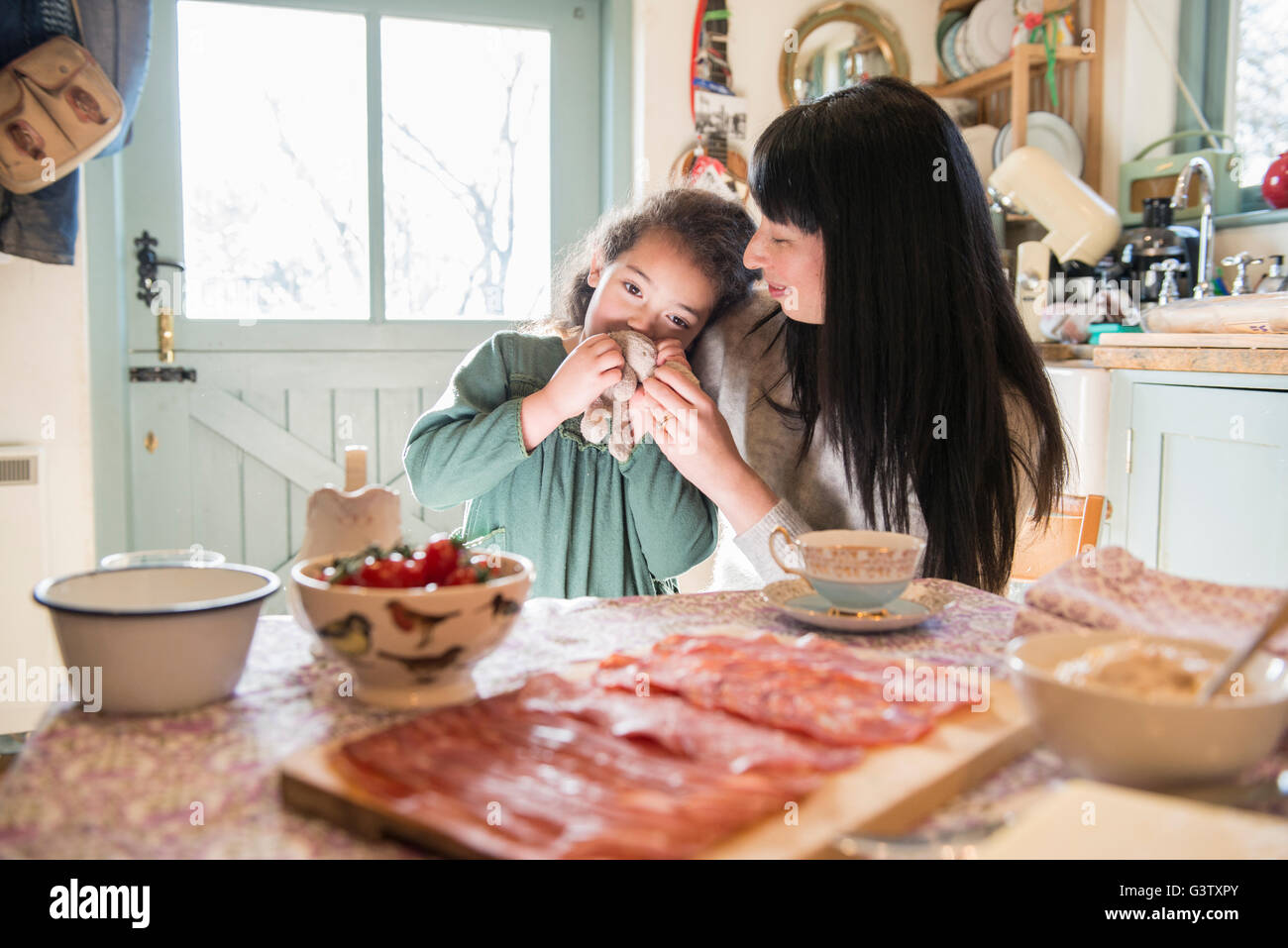 A six year old girl being comforted by her mother at the dinner table. - Stock Image