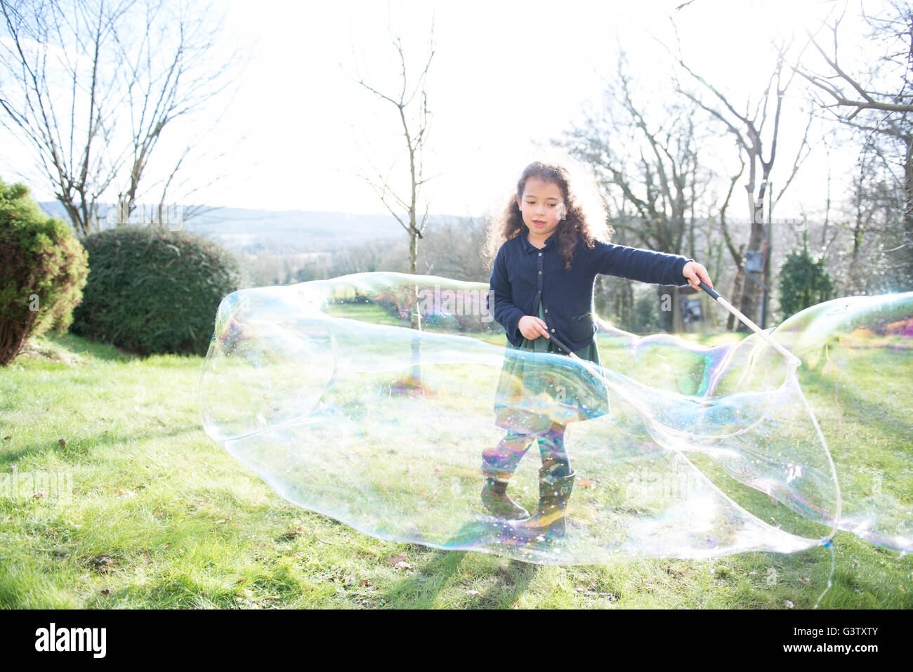 A six year old girl creating enormous bubbles in a garden. - Stock Image