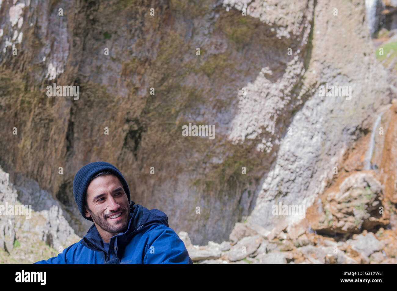 A mountaineer sitting in rugged terrain. - Stock Image
