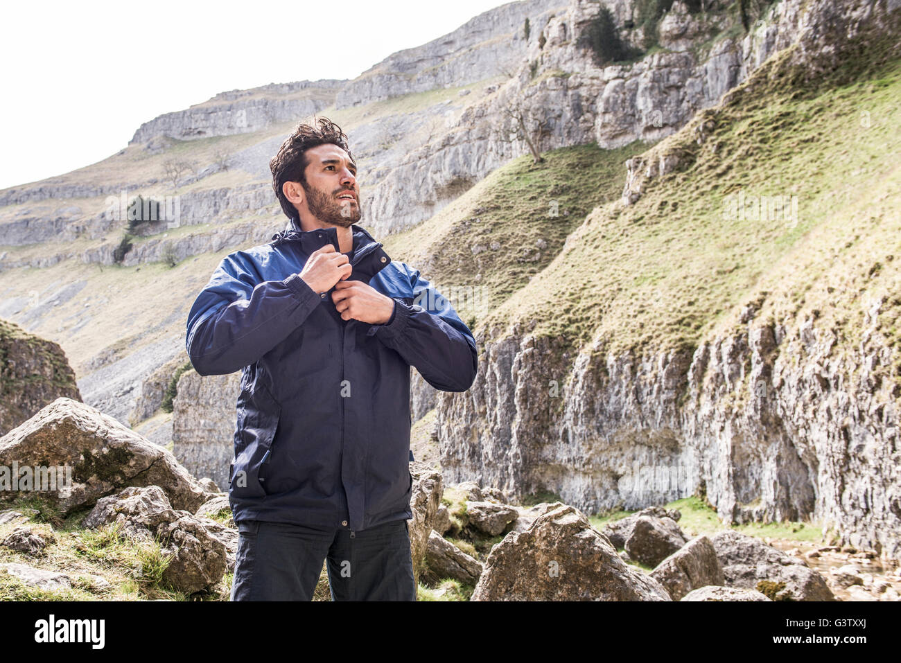 A mountaineer standing in rugged terrain. - Stock Image