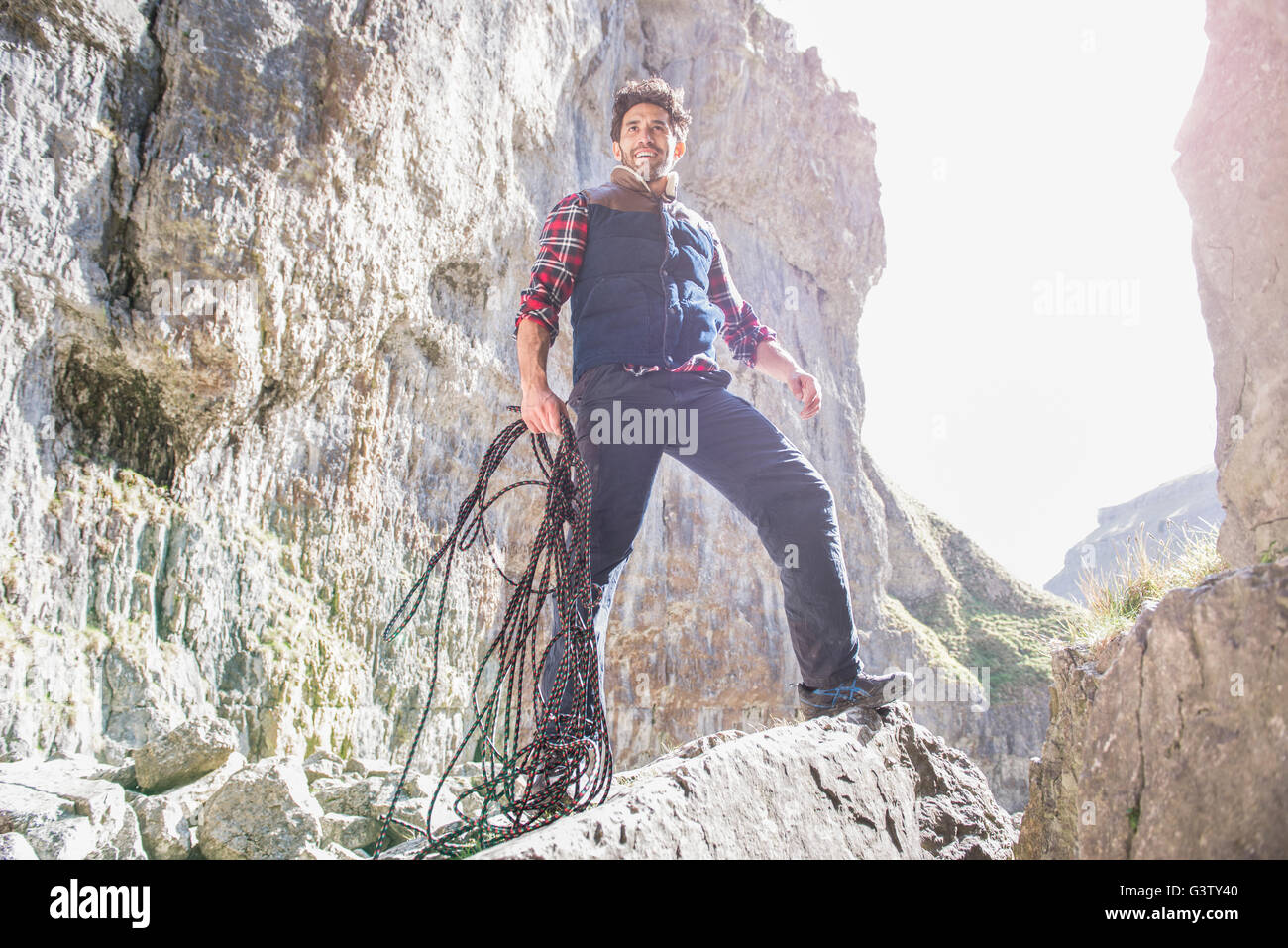 A mountaineer standing with a rope in rugged terrain. - Stock Image