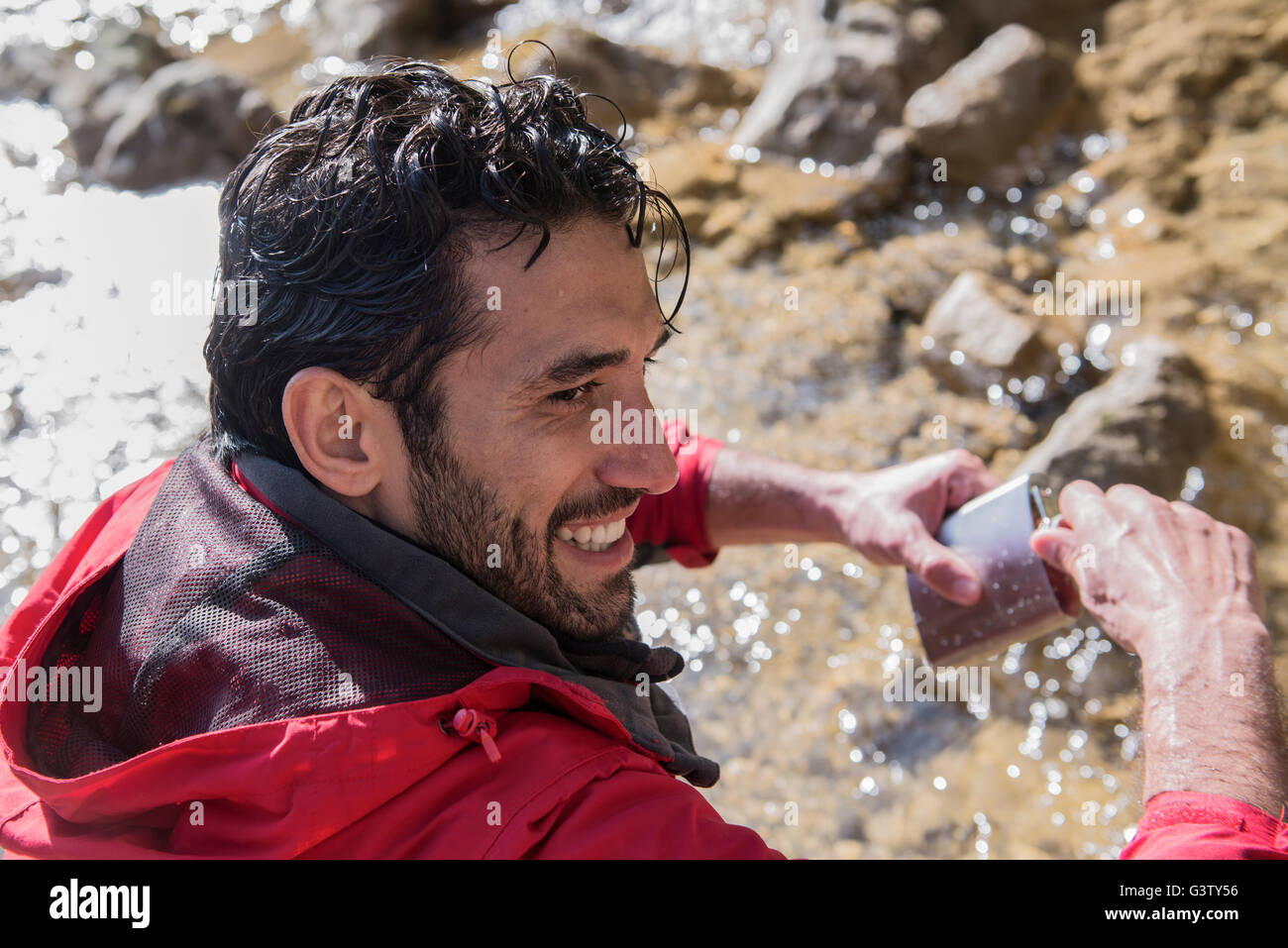 A mountaineer filling his water bottle from a mountain stream. - Stock Image
