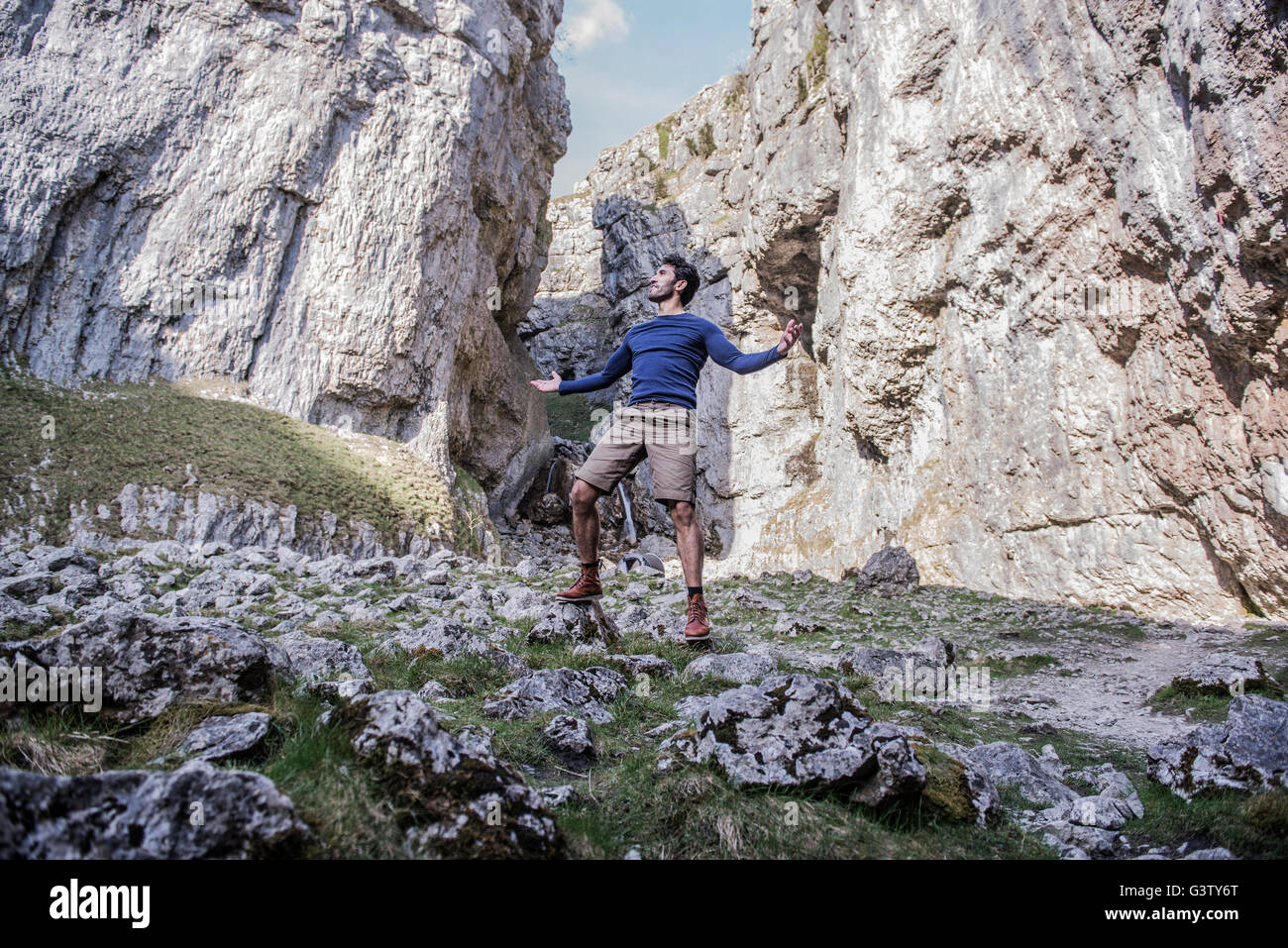 A man standing with arms aloft in rugged terrain. - Stock Image