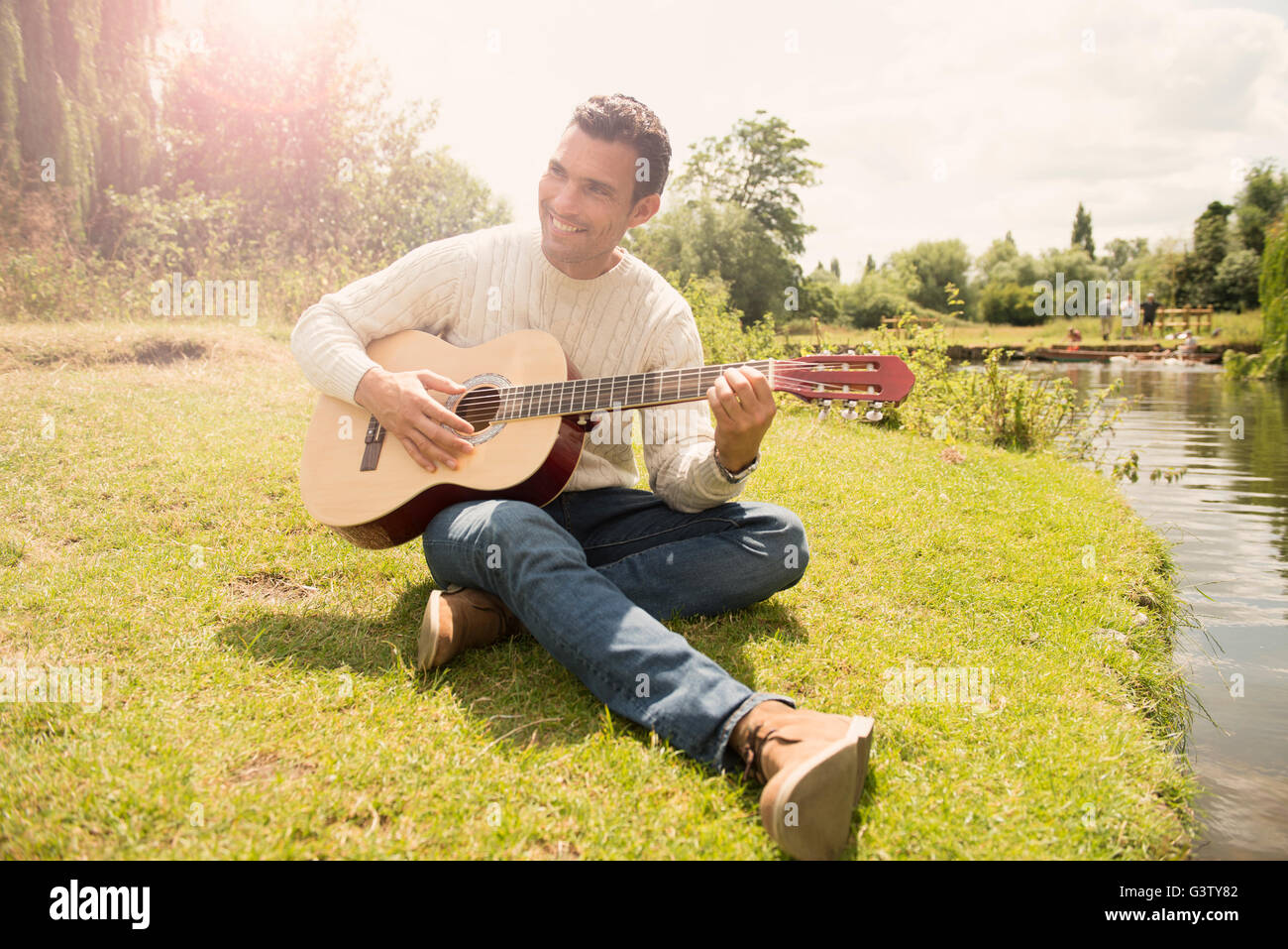 A man playing a guitar by the banks of the River Cam in Cambridge. - Stock Image