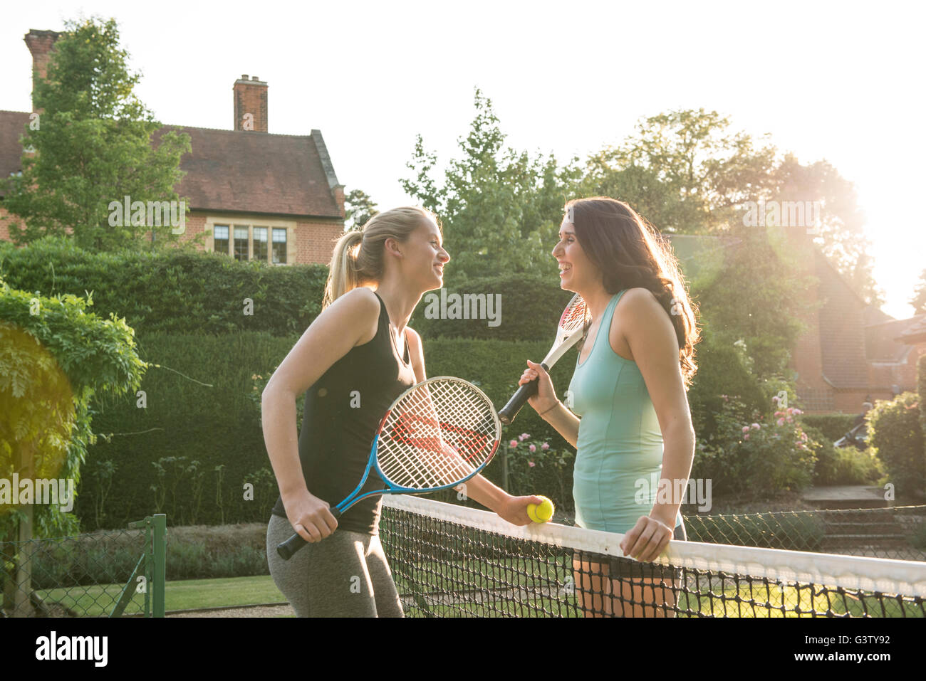 Two young women sharing a joke on a tennis court in the evening sunshine. - Stock Image