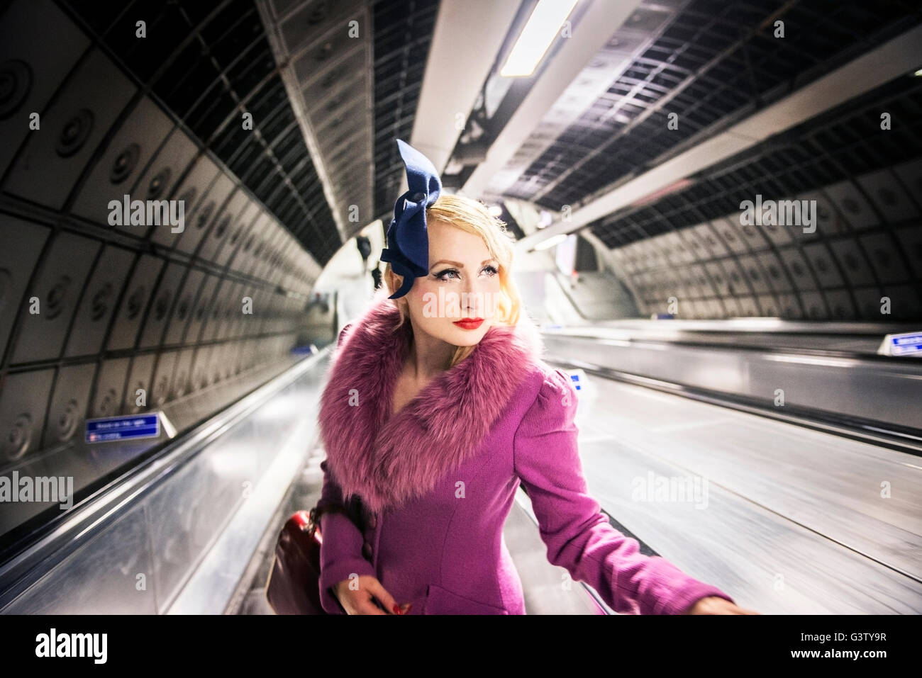 A stylish young woman dressed in 1930s style clothing on a London Underground escalator. - Stock Image