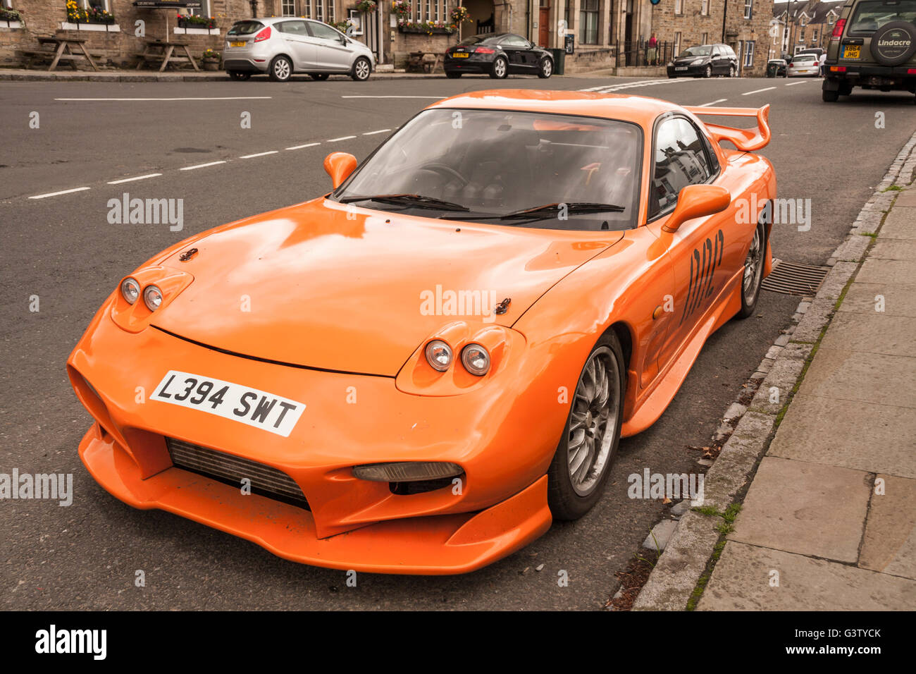 Orange Coloured Mazda RX7 Sports Car Parked In The Village Of  Middleton In Teesdale