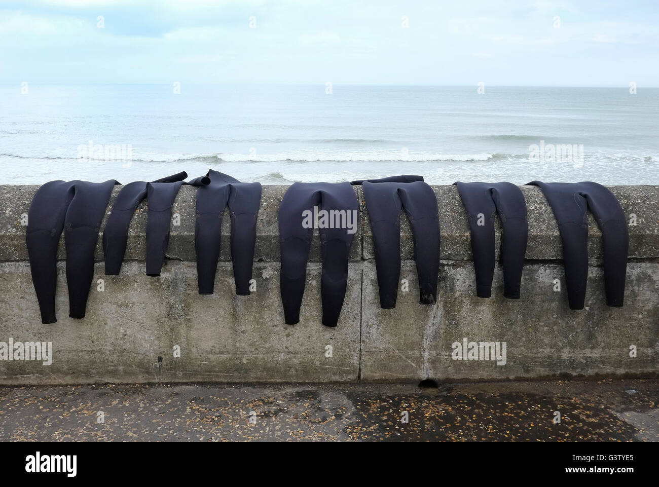 black wet suits drying out on concrete sea wall - Stock Image