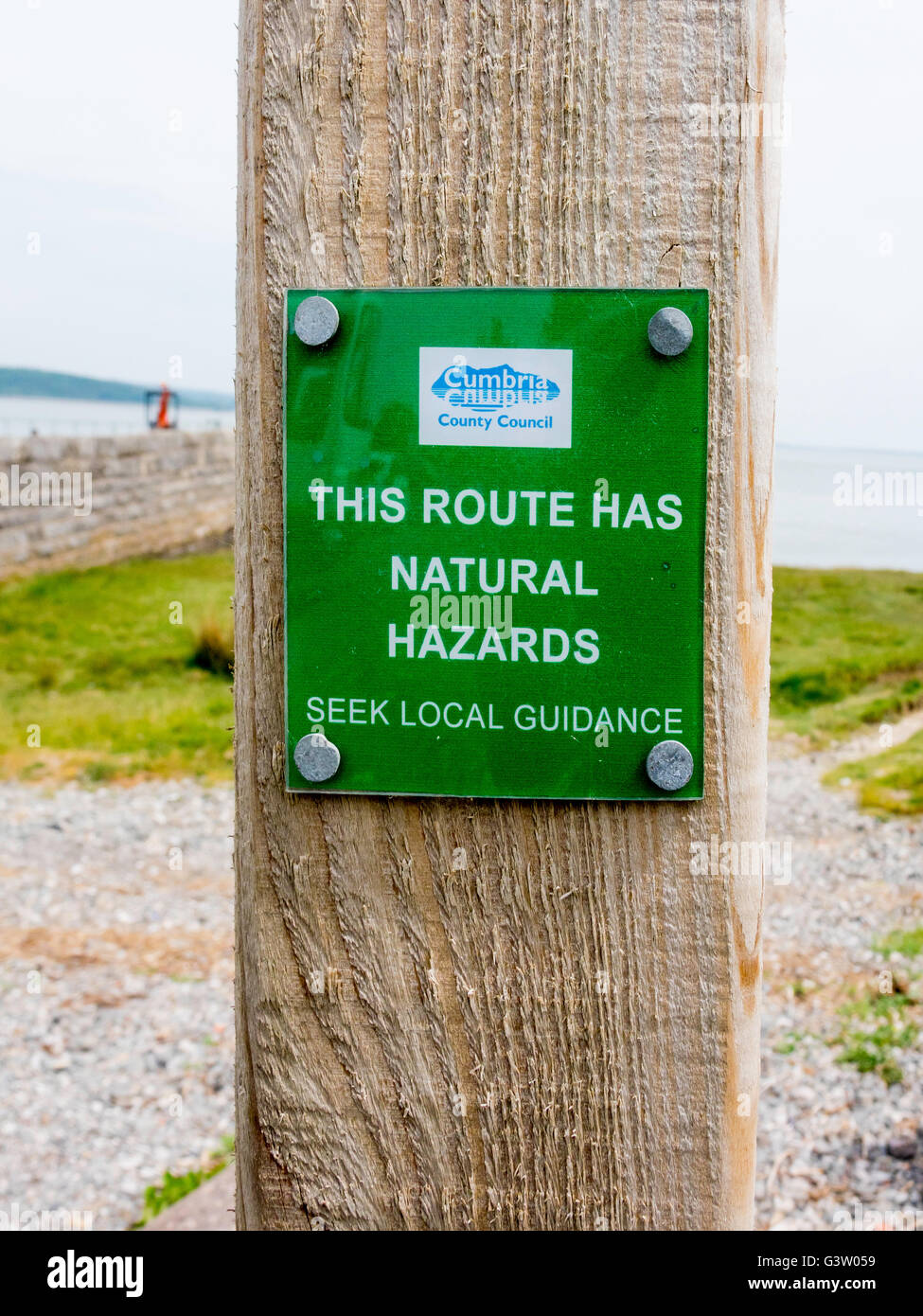 Cumbria County Council warning sign notice This Route Has Natural Hazards Seek Local Guidance foreshore footpath - Stock Image