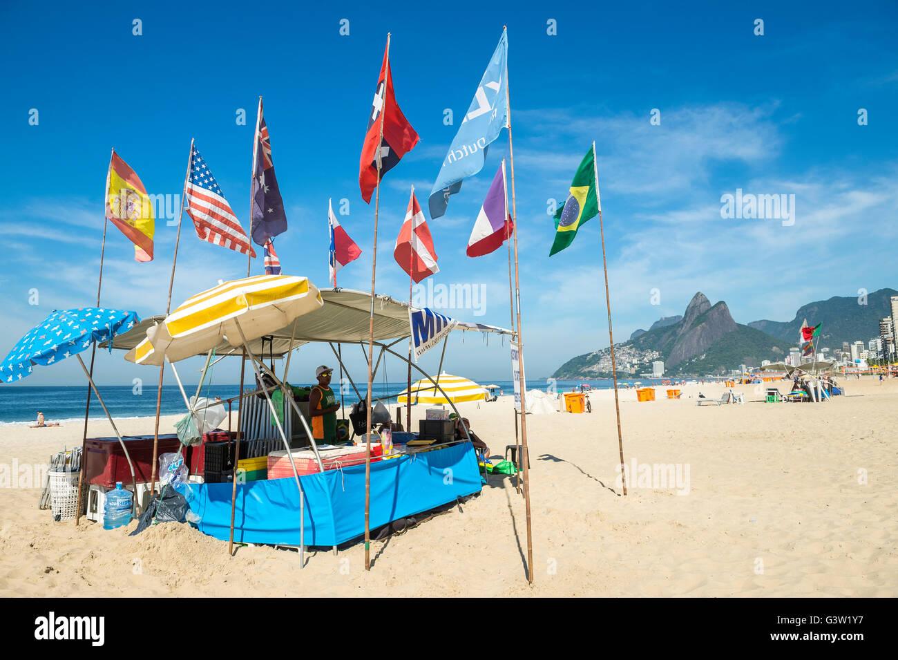 RIO DE JANEIRO - APRIL 4, 2016: International flags fly above a barraca (Brazilian beach shack) on Ipanema Beach. - Stock Image