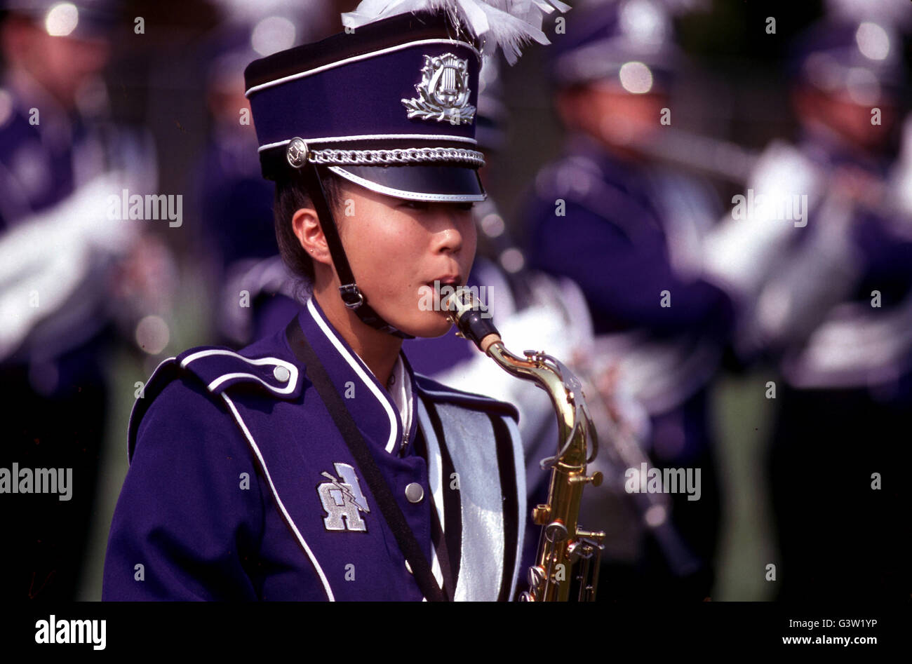 Member of marching band playing musical instrument at a halftime football game show - Stock Image