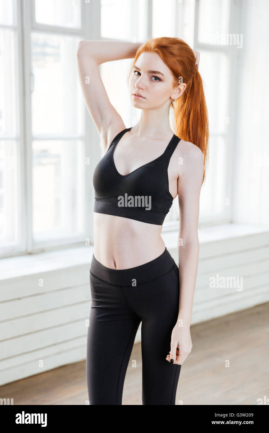 Attractive young girl with red hair wearing sport uniform standing at the gym - Stock Image