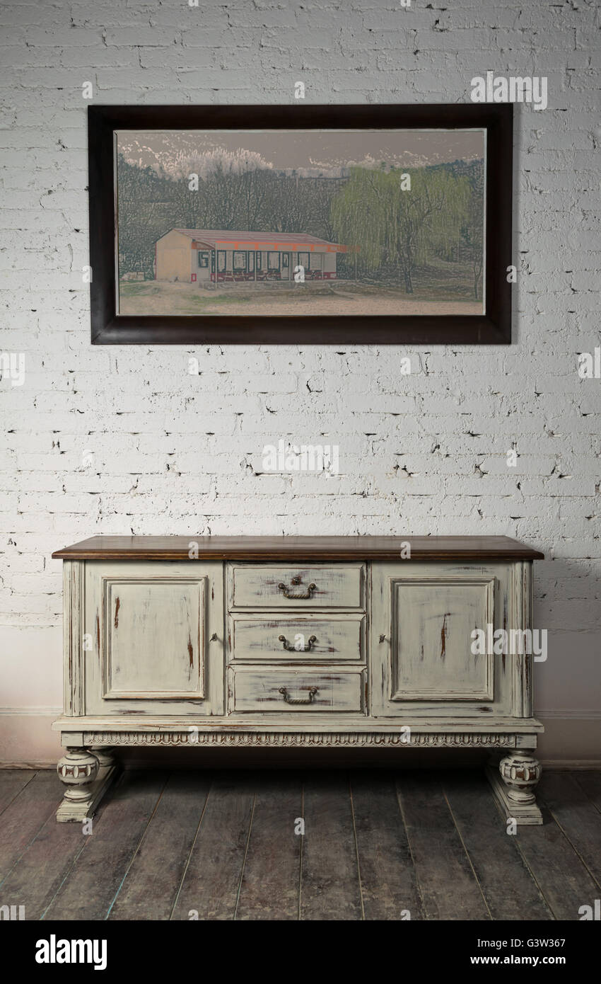 Still Life Of Vintage White Sideboard And Hanged Framed Painting On A Dark  Wooden Floor And