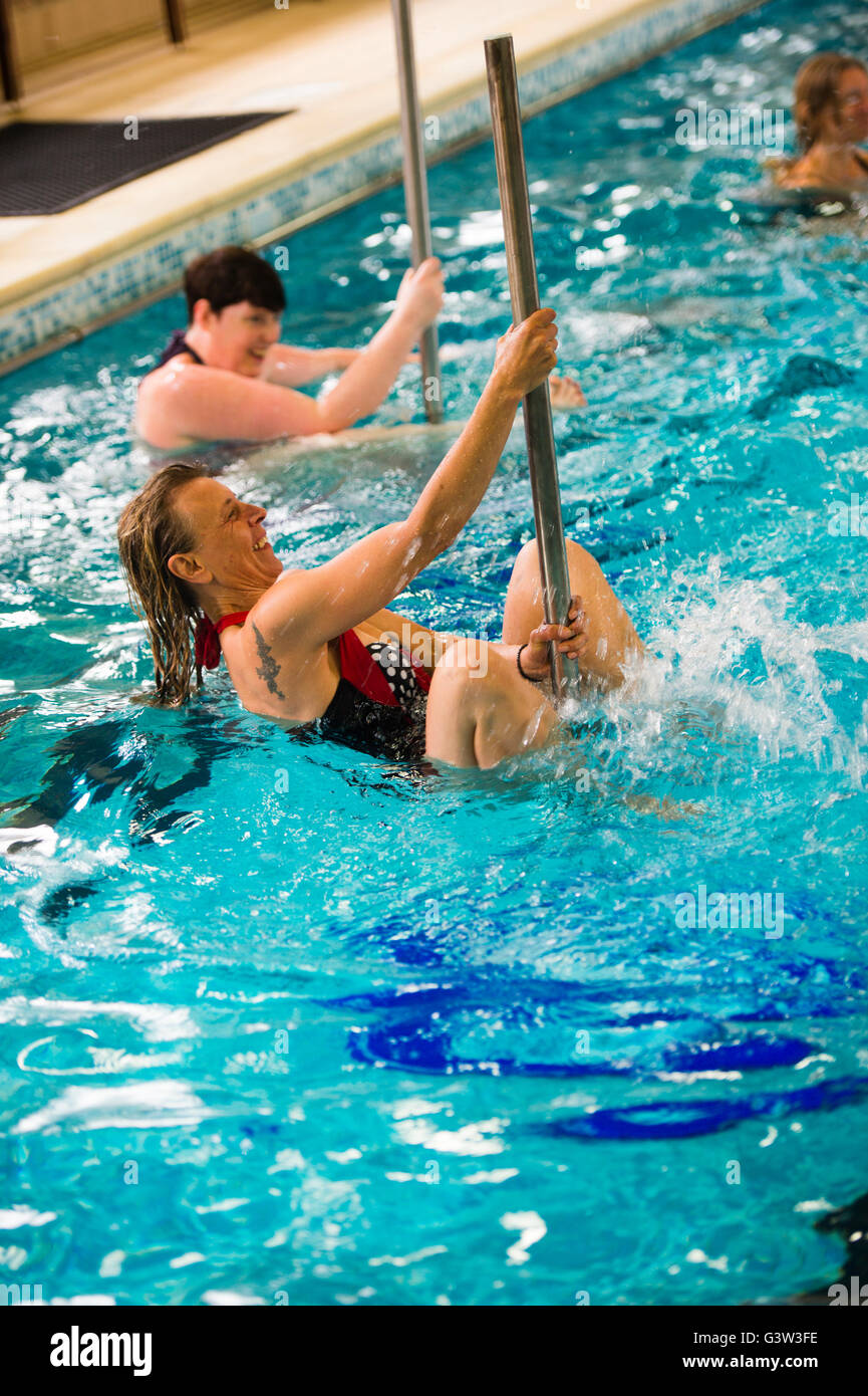Hydropole swimming pool fitness class: A group of adult mature senior women  taking part in a 'hydropole' pole dancing fitness class in the water in a swimming pool, UK Stock Photo