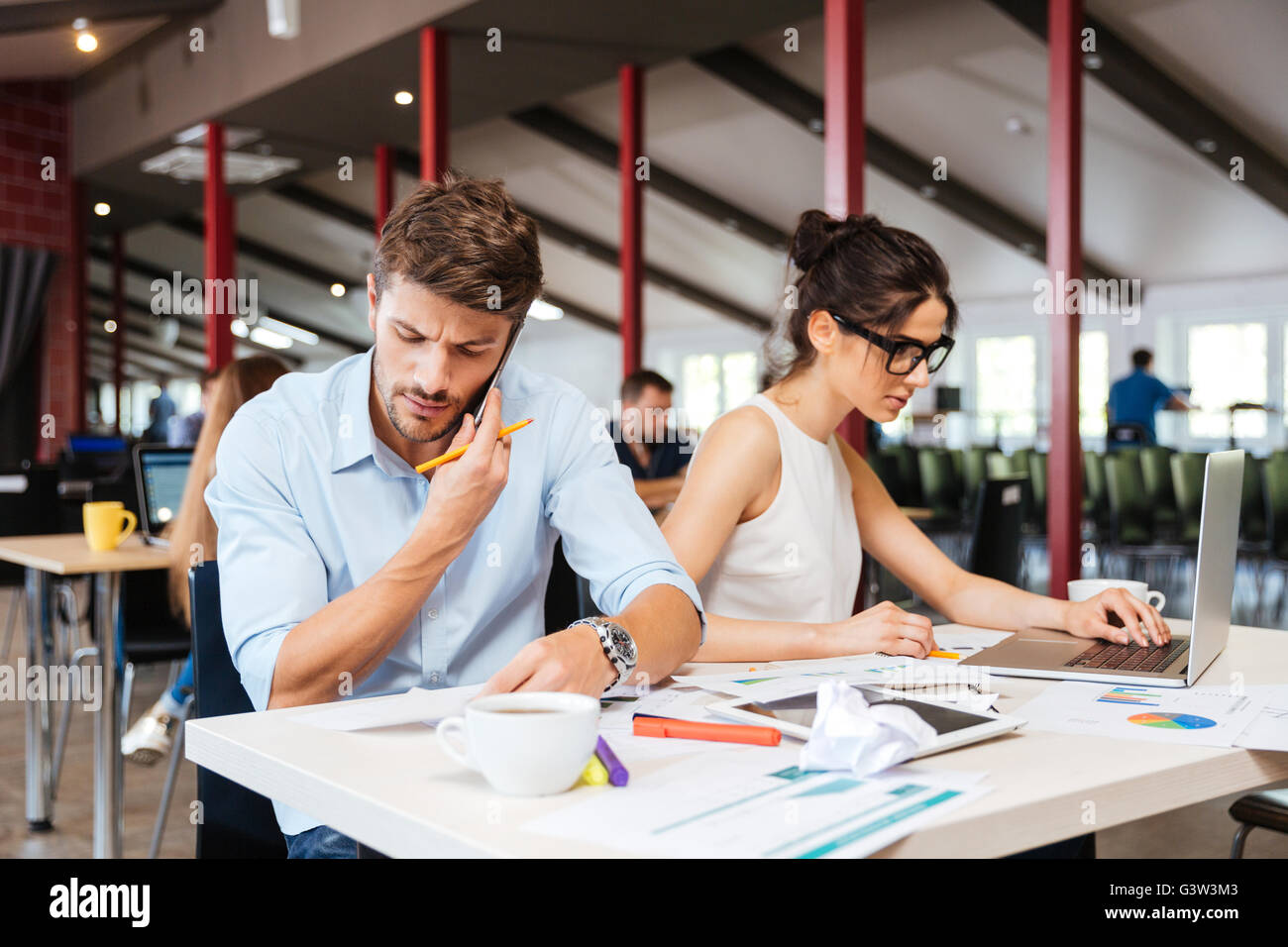 Focused young businessman and businesswoman sitting and working in office Stock Photo