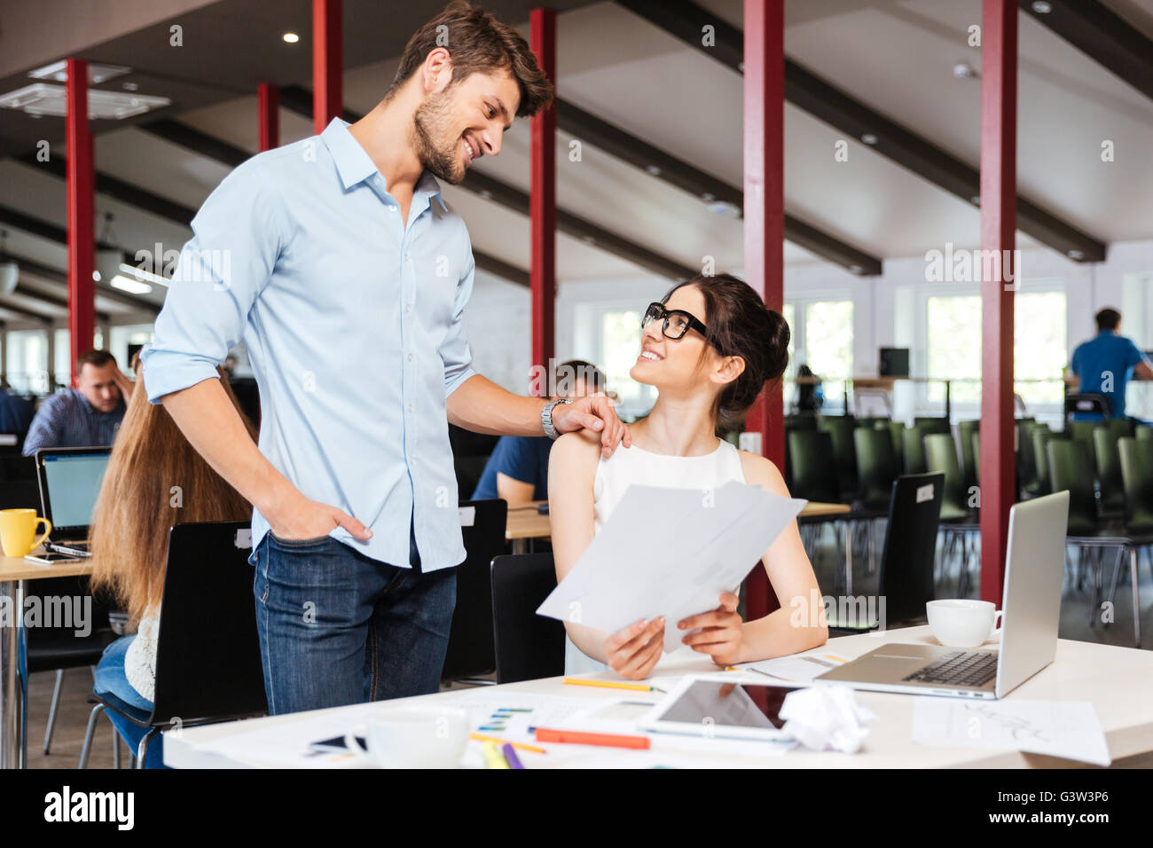 Two happy young business people smiling and working together - Stock Image