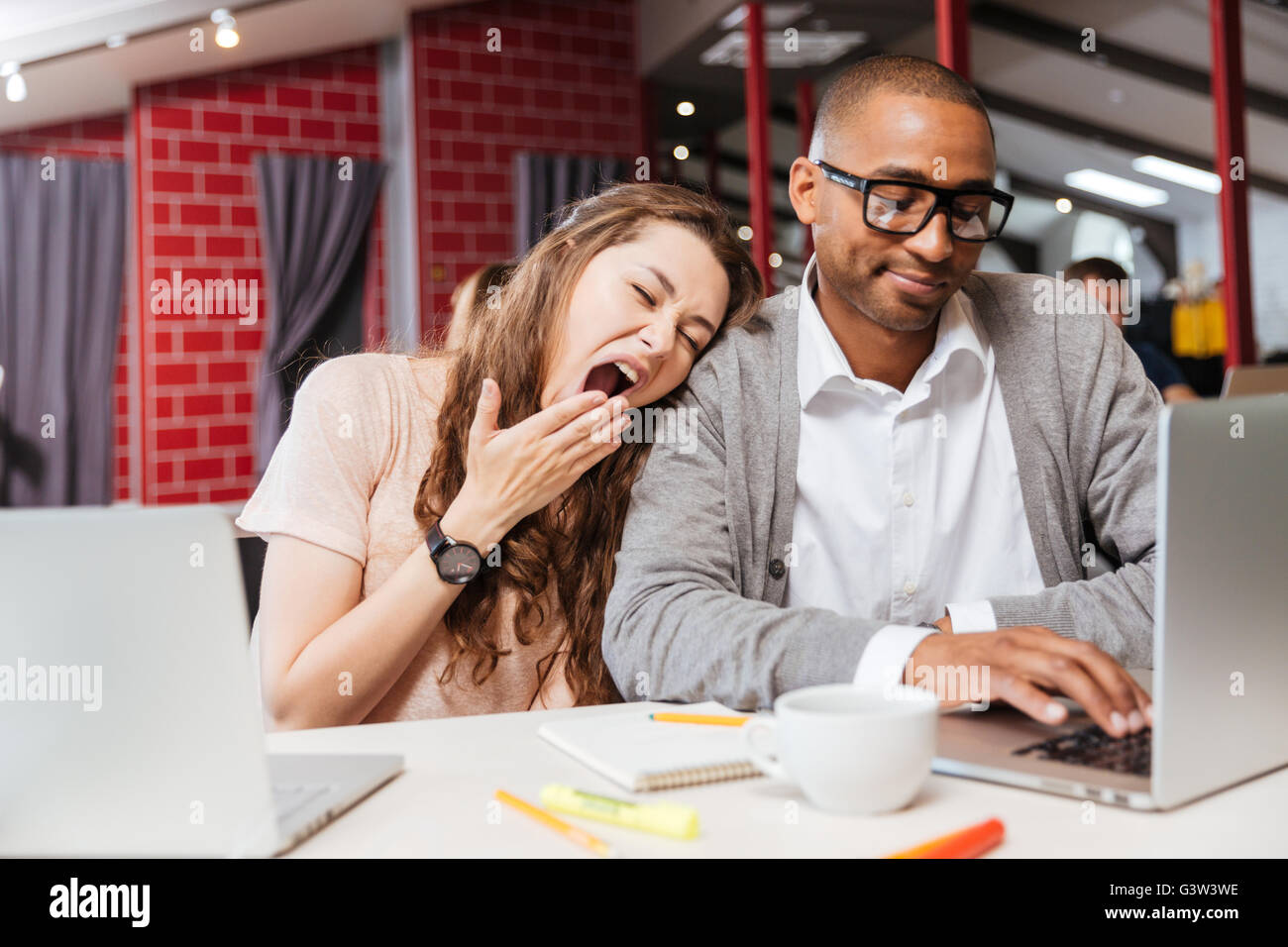 Tired bored young business people yawning and working with laptop in office - Stock Image
