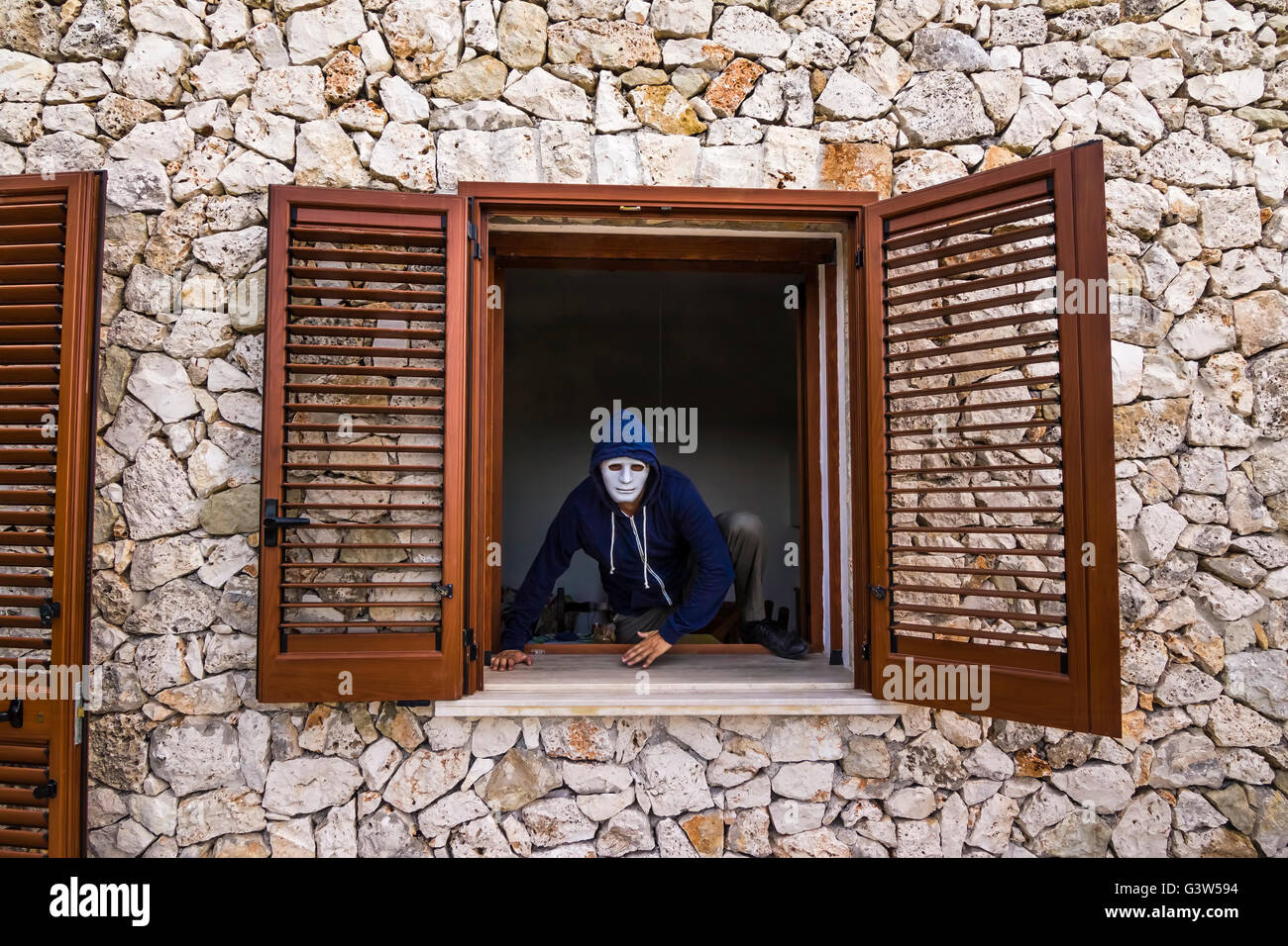 thief bypasses the window sill - Stock Image