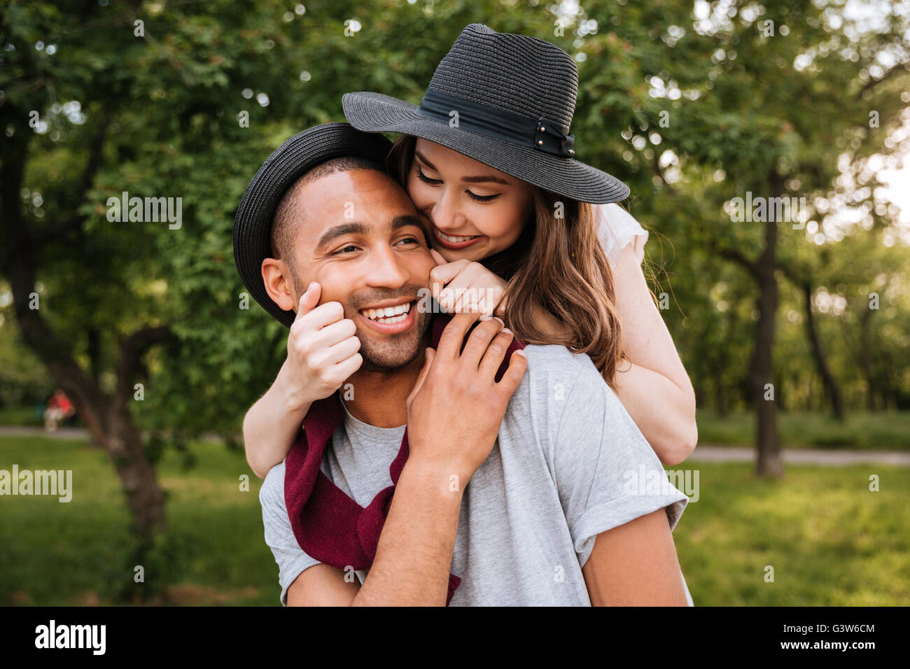 Smiling beautiful young couple in love having fun in park - Stock Image