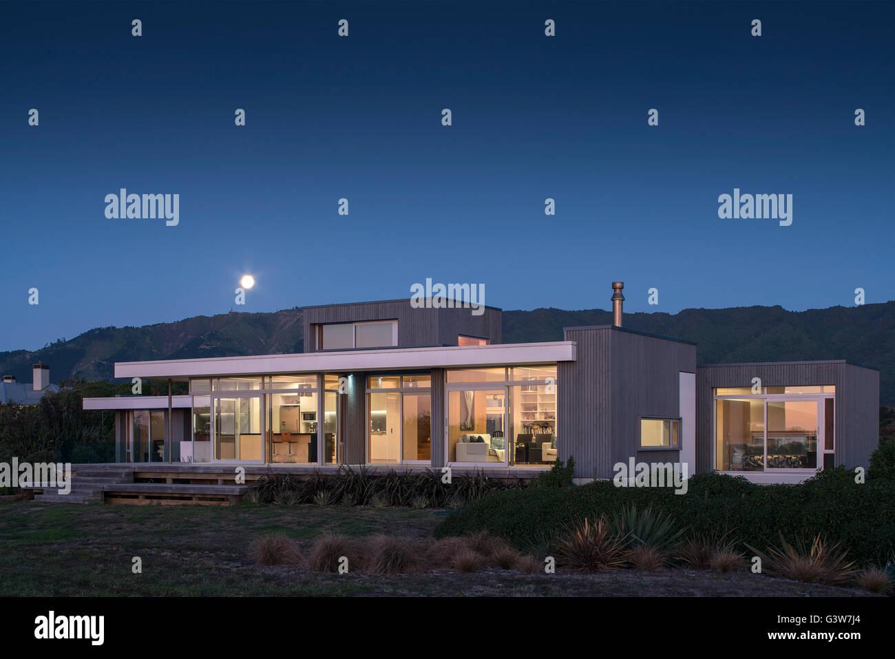 Moon rising over mountains, house lit up at dusk. Waikanae House, Peka Peka - Kapiti Coast, New Zealand. Architect: - Stock Image