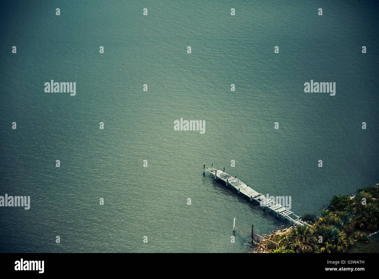 An aerial view of an old battered dock reaching into a blueish-green river/lake. - Stock Image