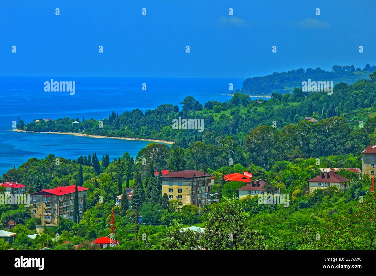 Panorama of sea coast with small resort cities and spurs of the mountain ridge covered by dense vegetation Stock Photo