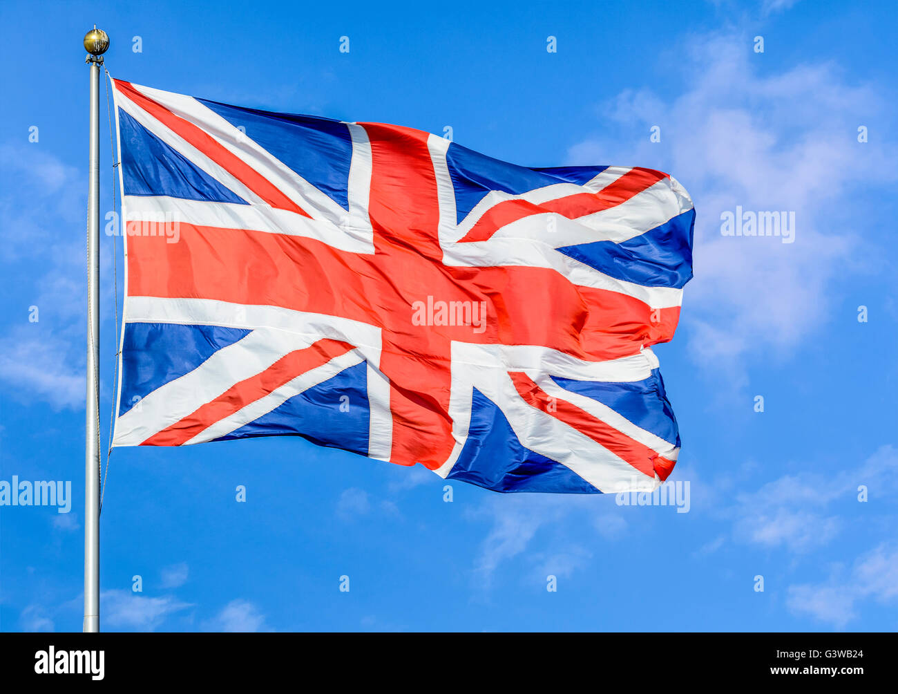 Union Jack flag of United Kingdom of Great Britain and Northern Ireland, flying on a pole against blue sky. - Stock Image