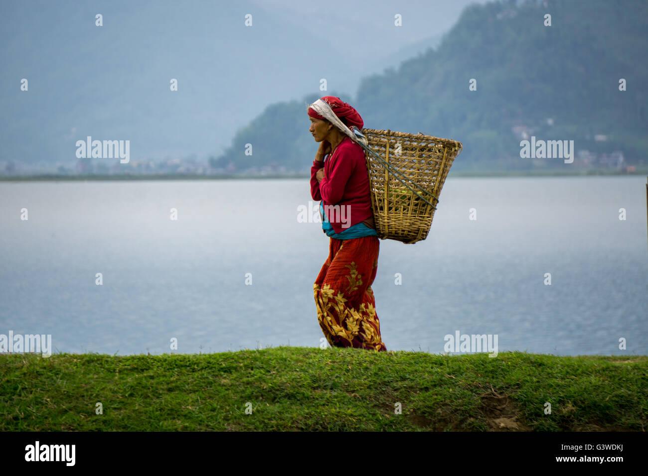 Woman carrying goods at Pokhara lake. - Stock Image