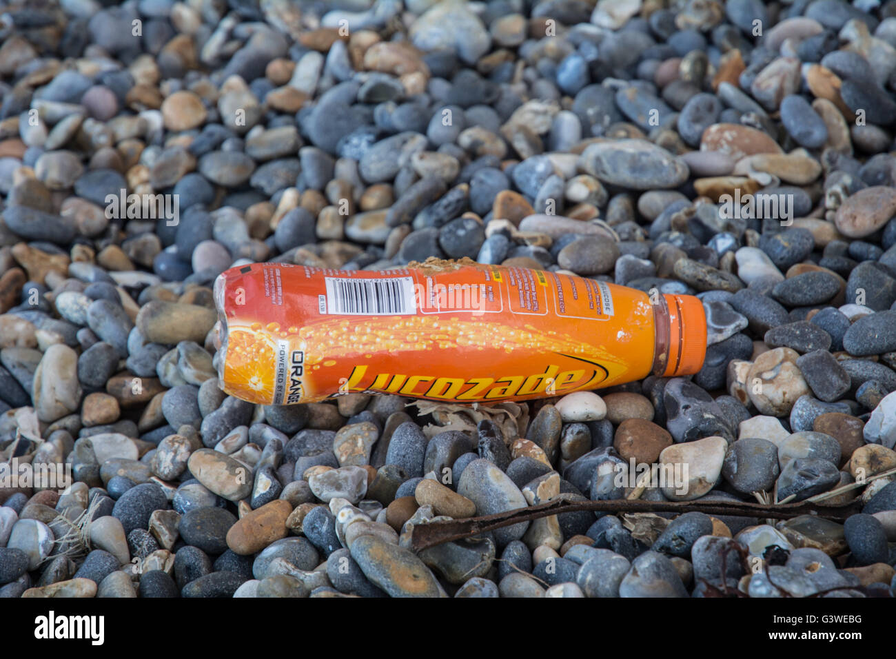 A Lucozade bottle on the floor at a stony beach in Norfolk. - Stock Image