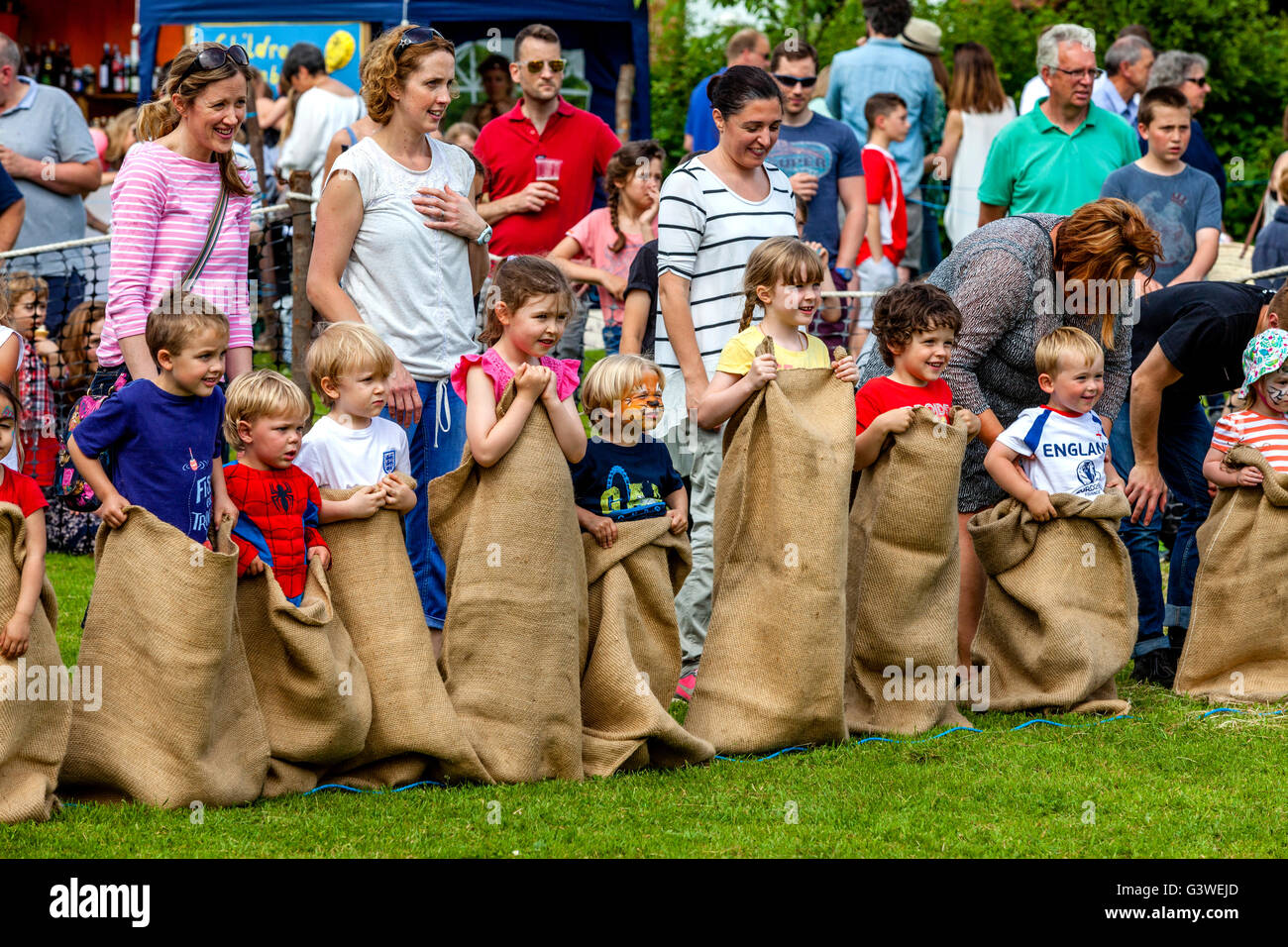 Children Prepare To Race In A Traditional Sack Race At The Medieval Fair Of Abinger, Surrey, UK - Stock Image