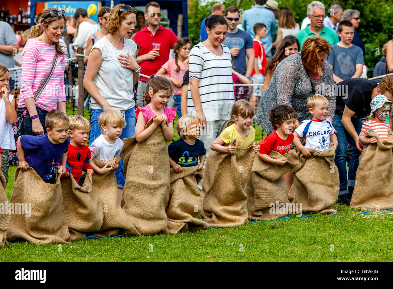 Children Race In A Traditional Sack Race At The Medieval Fair Of Abinger, Surrey, UK - Stock Image