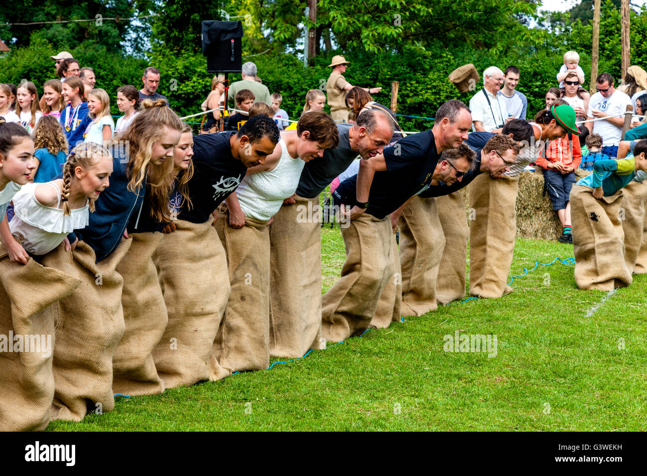 Teenagers and Adults Race In A Traditional Sack Race At The Medieval Fair Of Abinger, Surrey, UK - Stock Image
