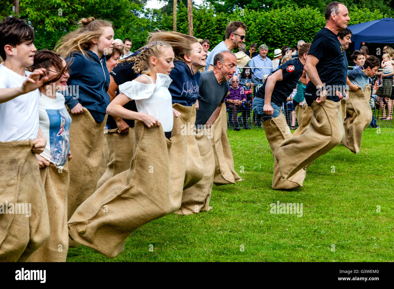 Teenagers and Adults Race In A Traditional Sack Race At The Medieval Fair Of Abinger, Surrey, UK Stock Photo
