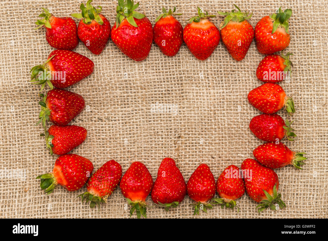 Frame made from fresh strawberries. Strawberries on the sackcloth. Decorative frame idea. Greeting card idea. - Stock Image
