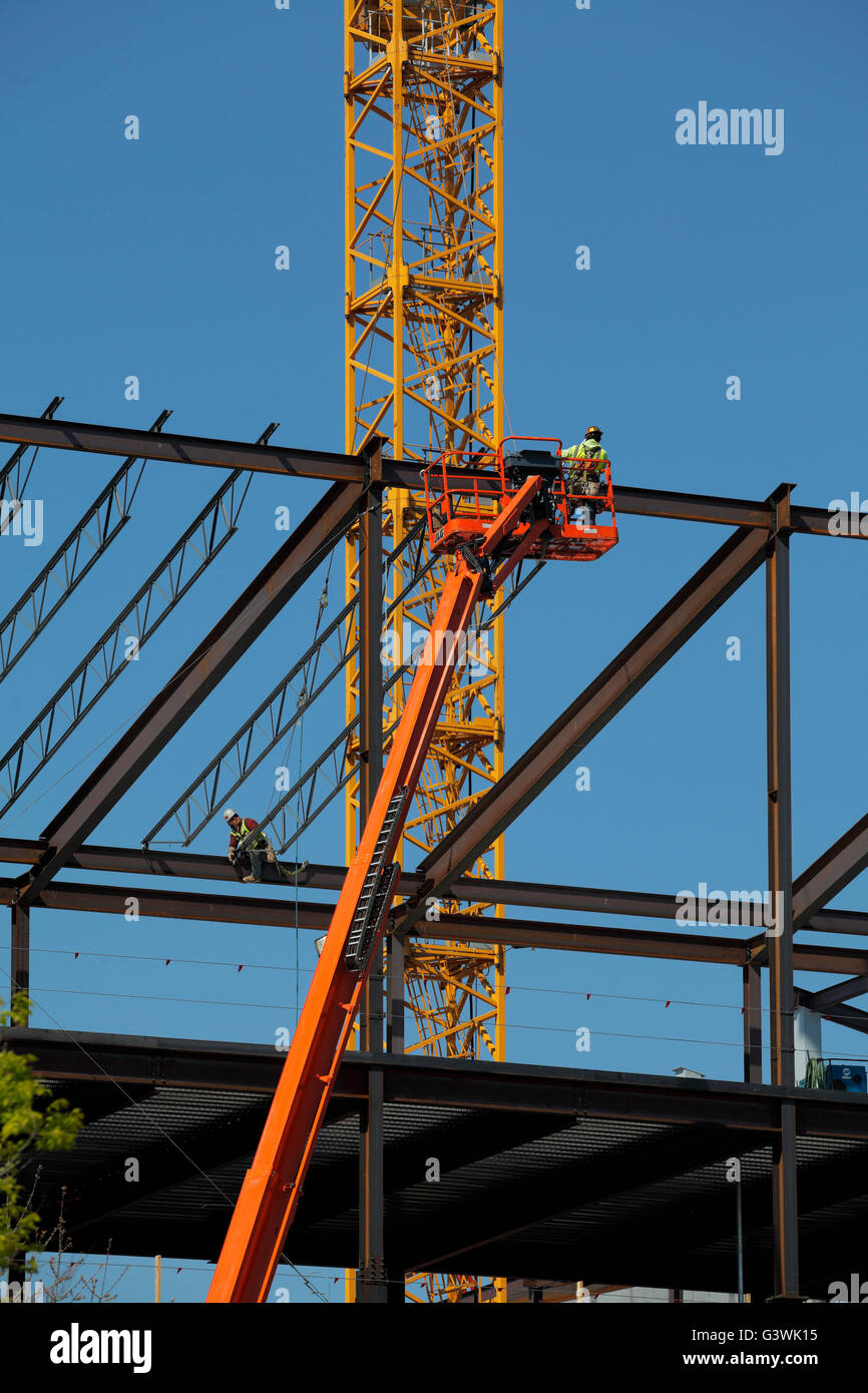 Steelworker working on the roof trusses of a new building. - Stock Image