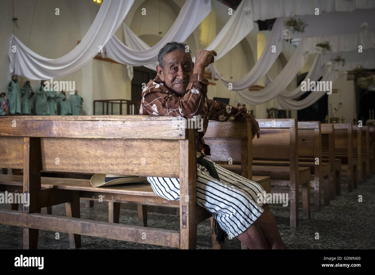 A devoted waits sitting in one of the pews of the church in Santiago Atitlan - Stock Image