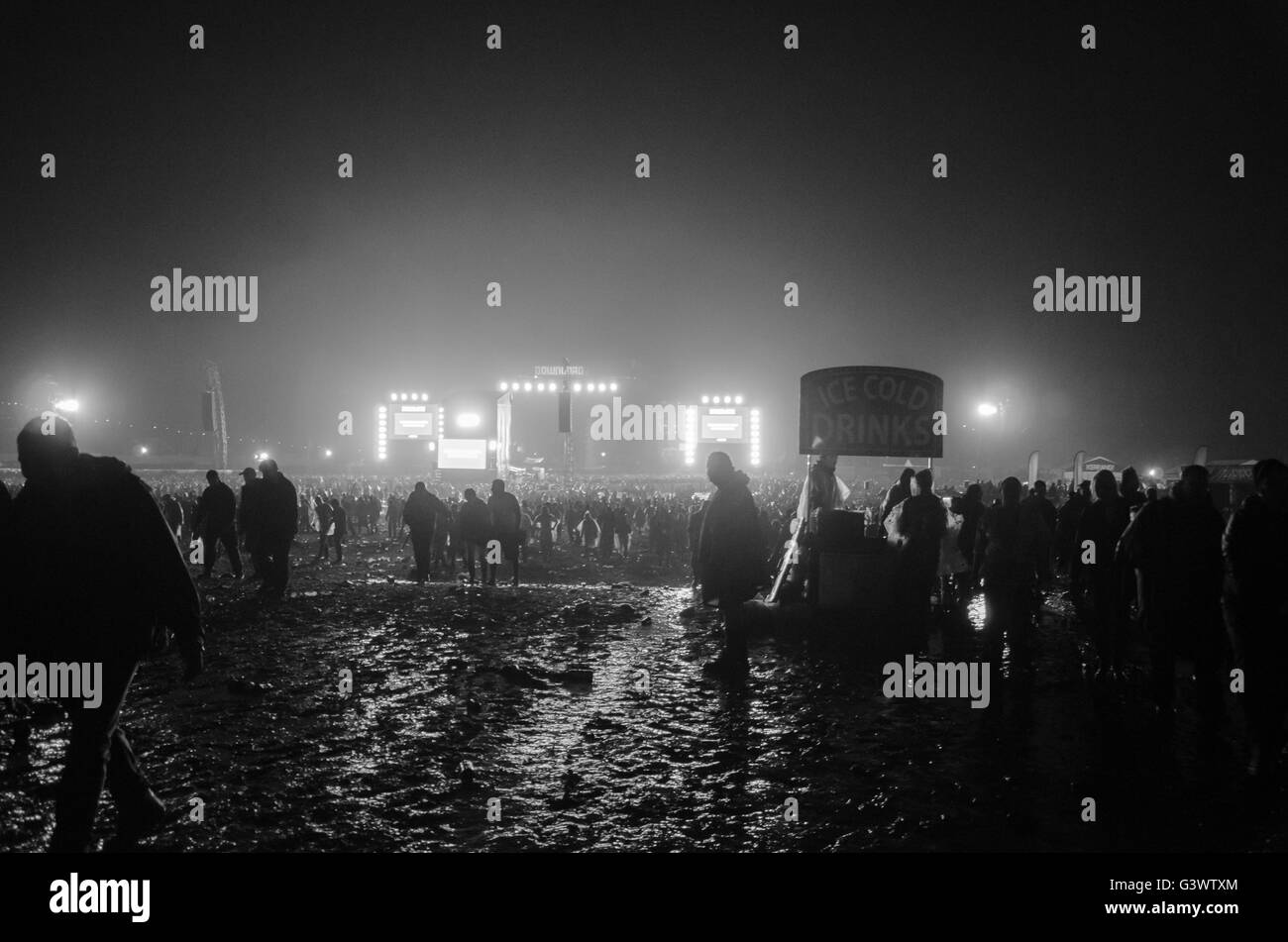 thousands of people leaving the main stage at download music festival late at night in mud after last band - Stock Image