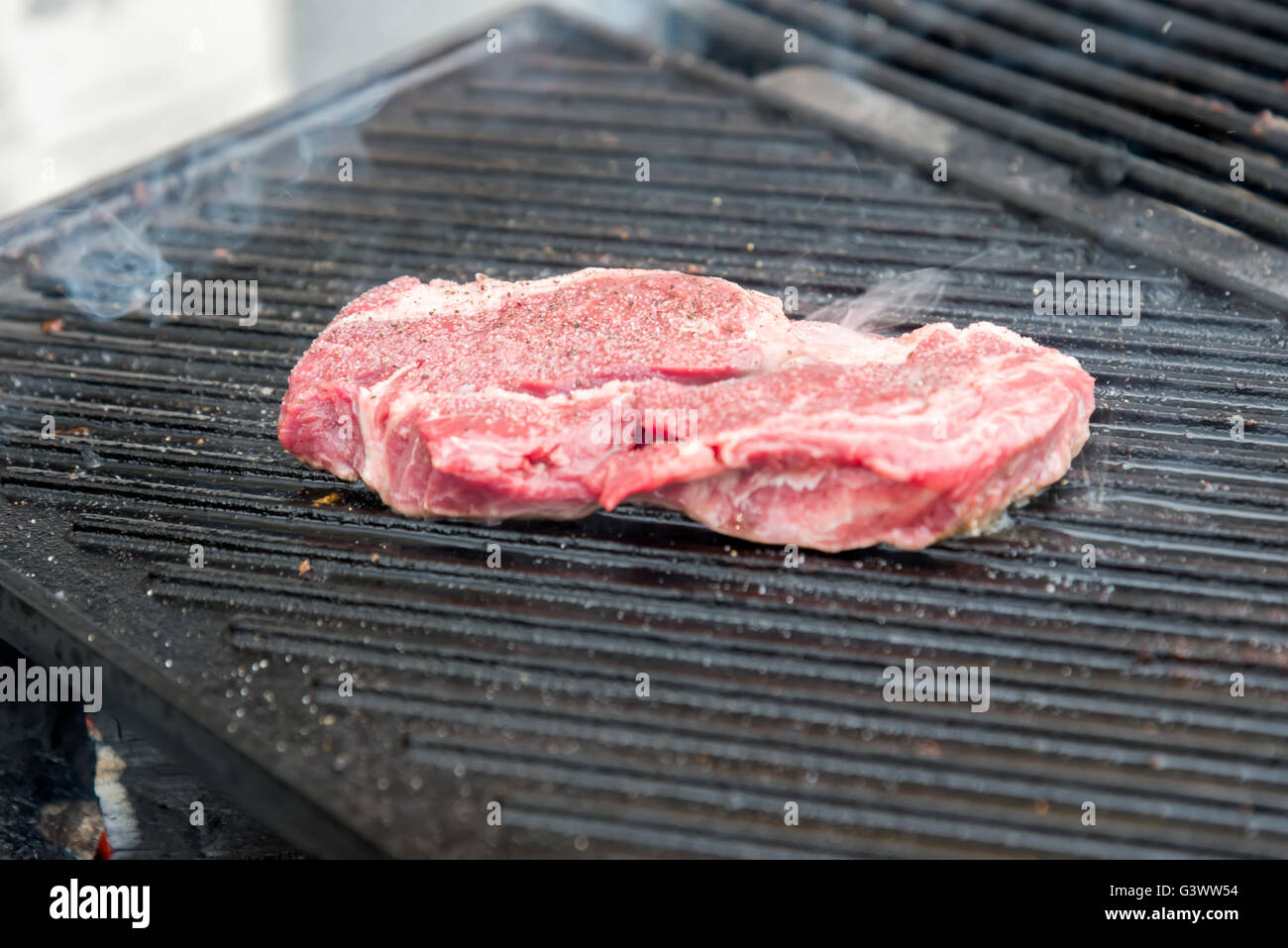 the raw steak with spices on metal grill - Stock Image