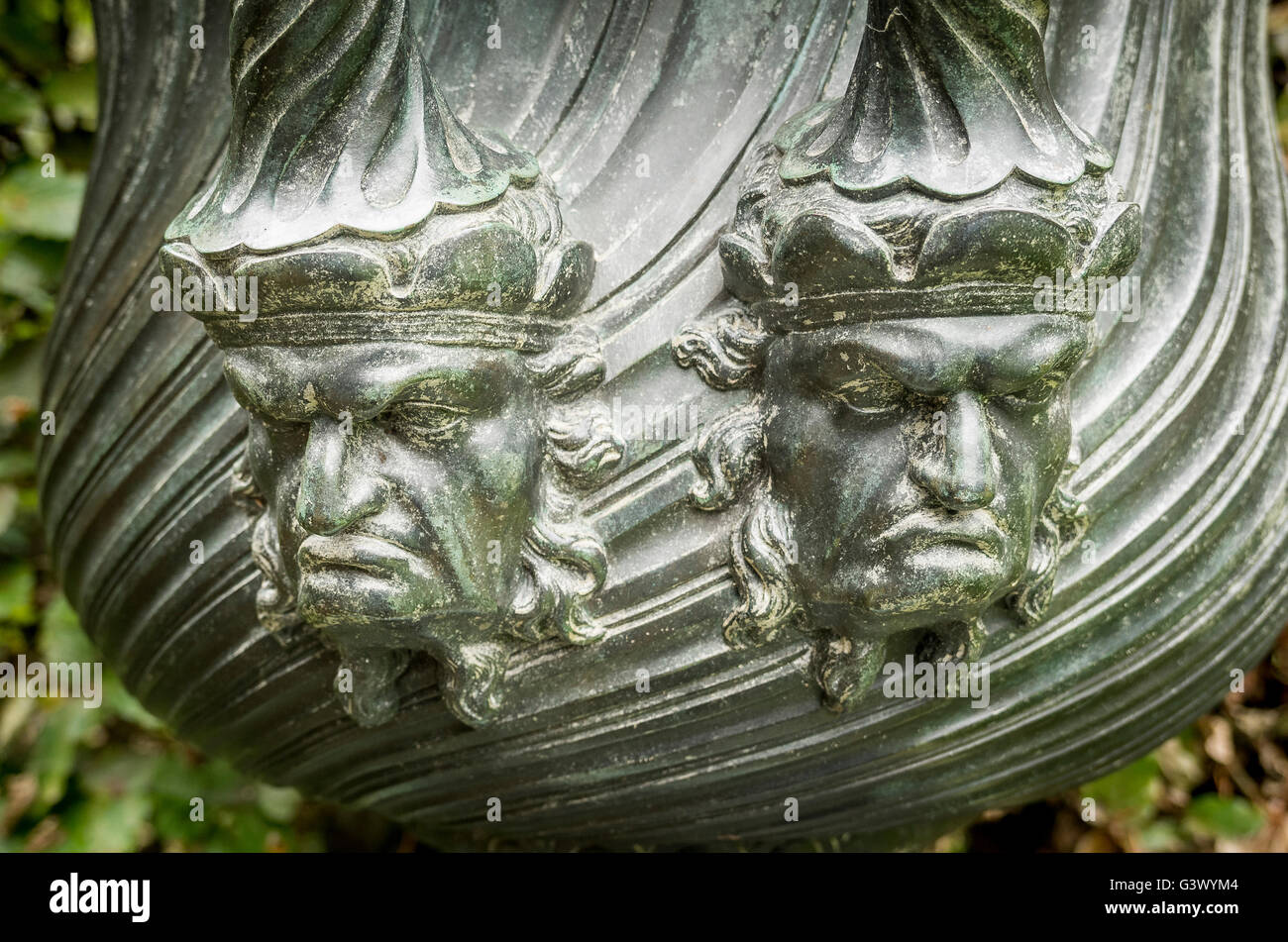 Two unhappy faces adorn an old urn in the garden of a stately home in UK - Stock Image